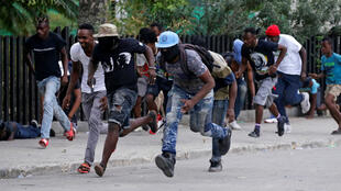 Protesters run for cover during a shooting in Champ de Mars, Port-au-Prince, Haiti, February 23, 2020.