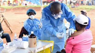 Un trabajador de una brigada sanitaria administra una vacuna contra el Ébola a una mujer que estuvo expuesta a la enfermedad en su aldea, el 18 de agosto de 2018.