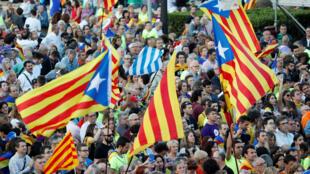 Personas sostienen Esteladas (banderas de la independencia catalana) a la salida de una manifestación a favor del referendo el 29 de septiembre de 2017.
