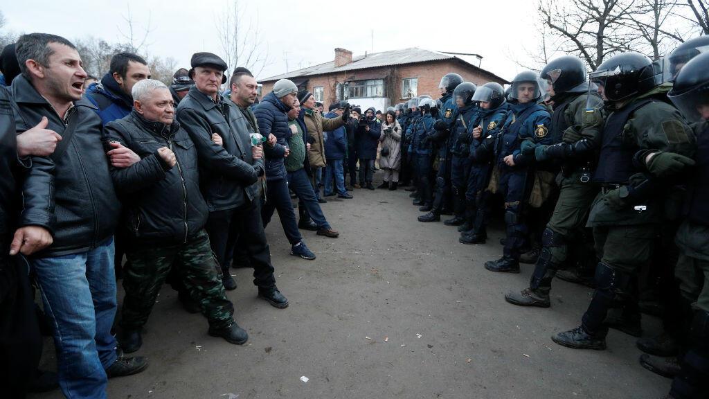 Manifestantes se alinean en Novi Sanzhary, Ucrania, frente a agentes ucranianos para protestar por la llegada de un avión que transportaba a los evacuados de la provincia china de Hubei, 20 de febrero de 2020