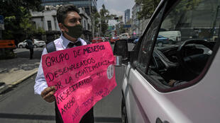 Un camarero desempleado sostiene un cartel mientras pide apoyo en las calles de Ciudad de México, el 14 de agosto de 2020