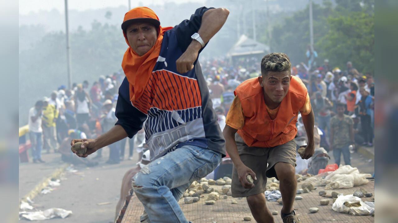 Manifestantes lanzan piedras en enfrentamientos con las fuerzas de seguridad venezolanas en el puente internacional Francisco de Paula Santander que une Colombia y Venezuela, el 23 de febrero de 2019.