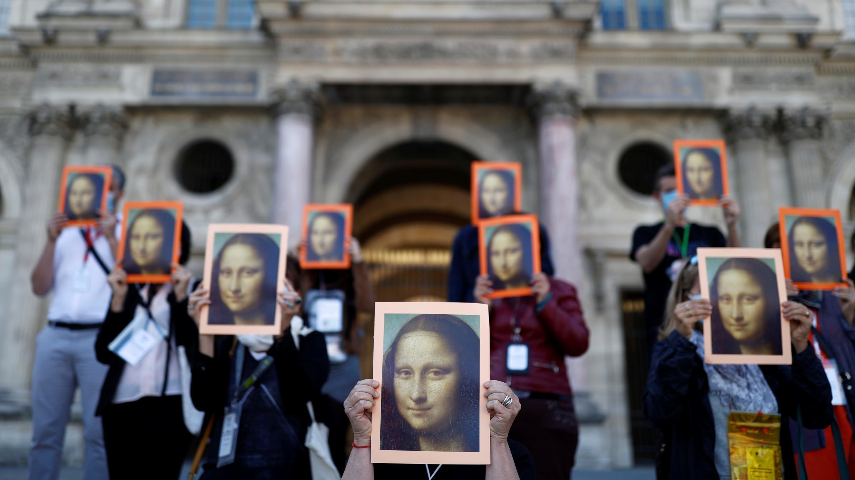 Los guías turísticos de París sostienen carteles que representan la pintura de Mona Lisa del artista Leonardo da Vinci durante una acción en el patio del museo Le Louvre para advertir sobre sus condiciones de trabajo en París. 6 de julio de 2020.