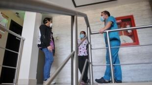El médico Jairo Rojas (i), la enfermera Alejandra Campos (c) y el médico Javier Palacios (d) conversan en el hotel donde los trabajadores de la salud se alojan y aislan en Guayaquil, Ecuador