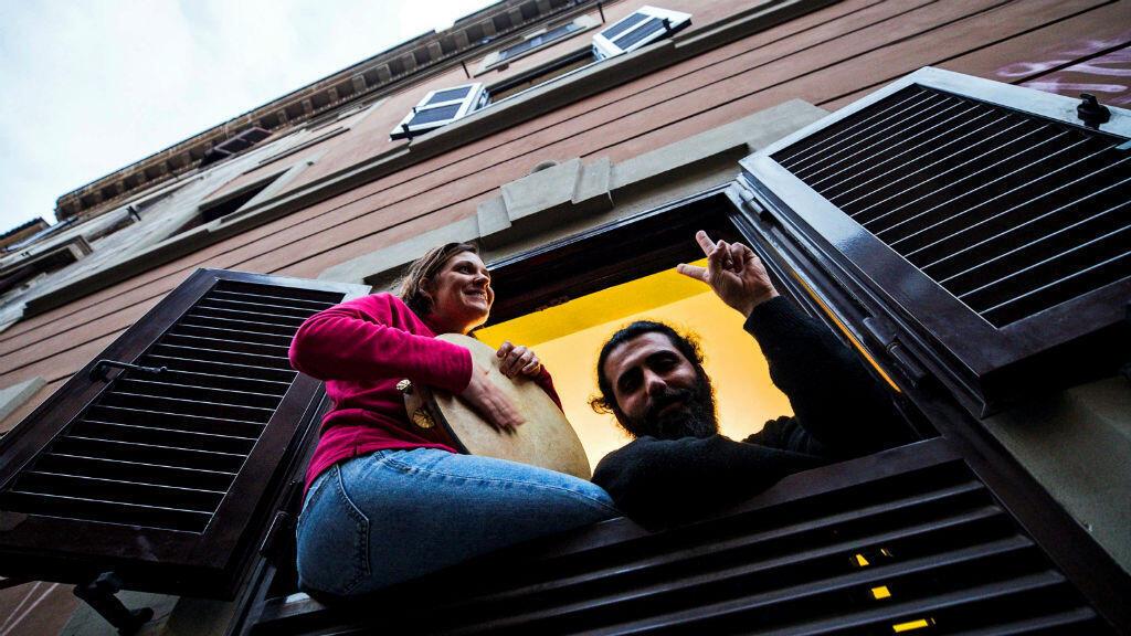 Las personas cantan desde la ventana de su casa durante un 'flashmob' lanzado en Italia para unir a las personas y tratar de hacer frente a la emergencia del coronavirus, en el distrito de Pigneto, en Roma, Italia, el 14 de marzo de 2020.