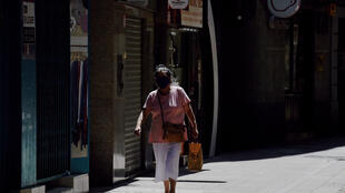 A woman wearing a face mask walks in Lerida in the Spanish region of Catalonia on July 13, 2020.