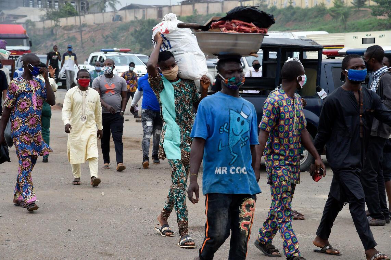 Des passants portent des masques à l'approche d'un contrôle de police à Lagos, au Nigeria, le 1er mai 2020.