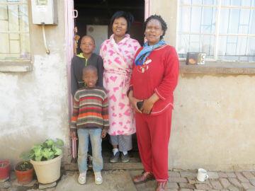 Maria Mahlangu (en rouge) et trois de ses enfants, Sugu, 25 ans, en peignoir rose, Zweli, 9ans, et Pride, 7 ans.