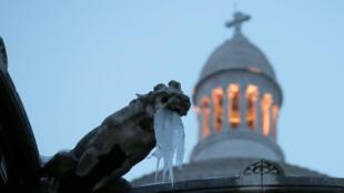 Carámbanos cuelgan de una gárgola en la basílica Sacre Coeur en Butte Montmartre en París mientras el clima invernal trae consigo nieve y temperaturas bajo cero a Francia, 9 de febrero de 2018.