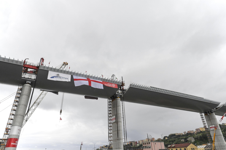 """L'Italie, réputée championne de lenteur dans l'exécution des travaux publics, met les bouchées doubles et achève en avril le pont, au point que l'on parle aujourd'hui dans la péninsule du """"modèle de Gênes"""". Le dernier tronçon du pont, long d'environ 1km, a été posé fin avril et depuis les travaux de finition et les tests de sécurité se sont succédés pour permettre son inauguration finale. Il y a une dizaine de jours, 56camions d'un poids de 44tonnes chacun, pour un total d'environ 2500tonnes, ont ainsi testé la solidité du pont."""