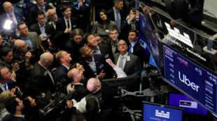 Representantes de la empresa Uber observan las cotización de las acciones de la compañía durante el debut en Wall Street el 10 de mayo de 2019