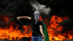 Un manifestante palestino sostiene una honda durante una protesta que marca el 70 aniversario de la Nakba, cerca del asentamiento judío de Beit El, cerca de Ramala, en Cisjordania, el 15 de mayo de 2018.