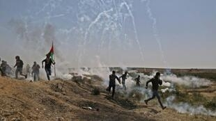فلسطينيون يفرون من الغاز المسيل للدموع خلال احتجاجات على حدود قطاع غزة، الجمعة 6 نيسان/أبريل 2018
