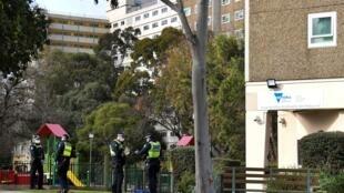 Des policiers devant un immeuble confiné à Melbourne (Australie) le 6 juillet 2020