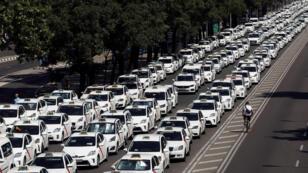 Taxistas bloquean una sección del Paseo de la Castellana, una de las principales avenidas de Madrid, durante la huelga contra los servicios de Uber y Cabify, el 30 de Julio de 2018.