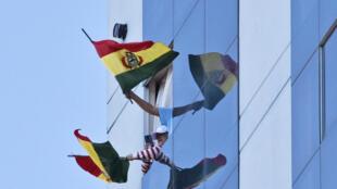 La gente ondea banderas bolivianas mientras una banda de música militar recorre las calles de La Paz, el 3 de mayo de 2020 durante la cuarentena obligatoria establecida por el gobierno a causa del coronavirus