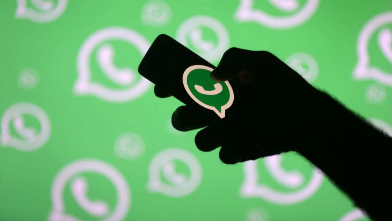 Un hombre posa con un teléfono inteligente frente a un logotipo de Whatsapp en esta ilustración.