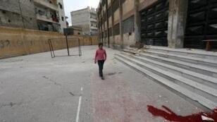 -فتاة تمر أمام بقعة دماء في مدخل مدرسة في حي الأنصاري بحلب - 12 نيسان/أبريل 2015