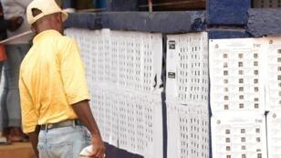 Un électeur libérien cherche son nom sur les listes à l'extérieur d'un bureau de vote à Monrovia, lors du second tour de l'élection présidentielle le 26 décembre 2017.