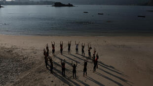 Varias mujeres se estiran al final de una clase de sedas en la playa Boa Viagem en Niteroi, Brasil.