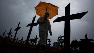 A workers wearing a protective suit and carrying an umbrella walks past the graves of COVID-19 victims in Manaus, Brazil -- the country has surpassed 250,000 deaths