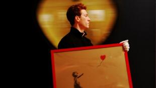 """Un empleado porta el cuadro """"Girl With Balloon"""" del artista Banksy, en la casa de subastas Bonhams en Londres, Reino Unido, el 23 de marzo de 2012."""
