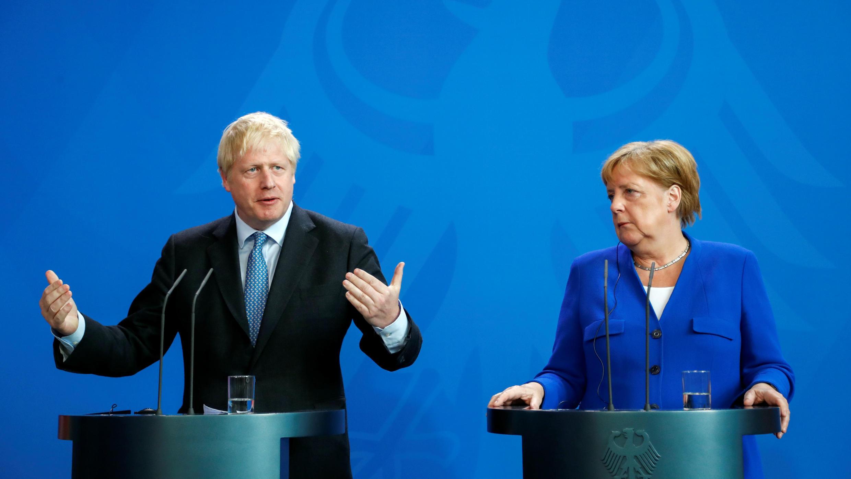 El primer ministro británico, Boris Johnson, hace un gesto mientras la canciller alemana, Angela Merkel, observa durante una conferencia de prensa en la Cancillería en Berlín, Alemania, el 21 de agosto de 2019.