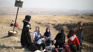 Kurds displaced by Turkey's Syrian offensive wait to cross into Iraq on October 21, 2019.