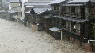 Men watch the swollen Isuzu River due to heavy rain caused by Typhoon Hagibis in Ise, central Japan, in this photo taken by Kyodo October 12, 2019.