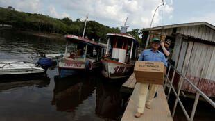 Un oficial electoral lleva una urna electrónica a la comunidad Nossa Senhora de Fátima, a lo largo del río Negro, estado de Amazonas, Brasil, el 6 de octubre de 2018.