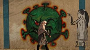 Une Palestinienne portant un masque de protection passe devant une fresque murale représentant un coronavirus, à Gaza (Territoires palestiniens) le 2 février 2021