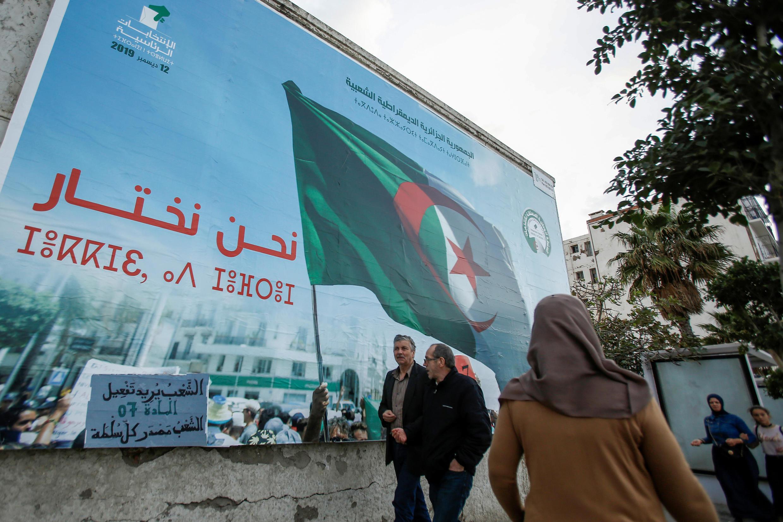 أشخاص يمشون بجوار ملصق حملة للانتخابات الرئاسية في الجزائر العاصمة، الجزائر، 2 نوفمبر/ تشرين الثاني 2019.