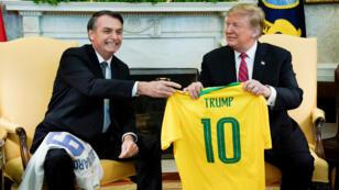 Le président brésilien, Jair Bolsonaro, remet un maillot de la Seleçao au président américain Donald Trump, après avoir reçu un maillot de l'équipe américaine de football, lors d'une réunion tenue le 19mars2019 dans le bureau Ovale de la Maison Blanche à Washington.