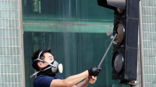 Un manifestant s'en prend à un feu rouge, le 20 octobre 2019, à Hong Kong.