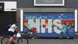 Un ciclista pasa por delante de una tienda cerrada con un grafiti dedicado a los sanitarios del Sistema Nacional británico en Hull, en el norte de Inglaterra, el 9 de mayo de 2020