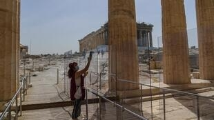 A worker (pictured May 18, 2020) wearing a protective mask cleans a divider made of plexiglass at the entrance of the Acropolis in Athens amid the pandemic of the novel coronavirus