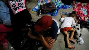 Migrantes hondureños, que forman parte de la caravana que intenta llegar a EE. UU., descansan en un refugio durante una nueva etapa de su viaje en Tecún Umán, Guatemala, el 18 de octubre de 2018.
