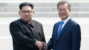 Le dirigeant nord-coréen, Kim Jong-un (gauche), et le président sud-coréen, Moon Jae-in, ont franchi symboliquement la ligne de démarcation des deux Corées, le 27 avril 2018.