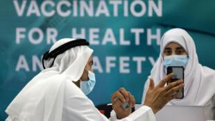 رجل يسجل بياناته قبل تلقي اللقاح المضاد لفيروس كورونا المستجد في مركز للتطعيم في دبي في 3 شباط/فبراير 2021