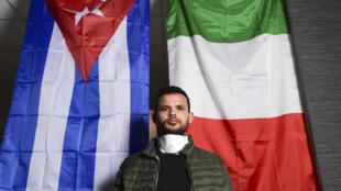 El doctor cubano Roberto Arias Hernández, especializado en medicina interna, posa delante de unas banderas cubana e italiana en el Hospital Maggiore de Crema, en el noroeste de Italia, el 15 de mayo de 2020