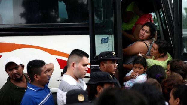 Migrantes hondureños, que forman parte de una caravana que intenta llegar a Estados Unidos, suben a un autobús después de un chequeo policial durante una nueva etapa de su viaje en Río Bravo, Guatemala, el 18 de octubre de 2018.