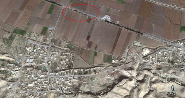 Vue satellitaire plus large. Encerclée en rouge : l'allée d'arbres qui corresponderait à l'arrière-plan des images vidéo. À gauche, la ville de Raqqa. L'exécution de James Foley aurait eu lieu sur la colline située au sud-est de la localité.