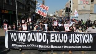 """Manifestantes portan una pancarta con la leyenda """"Yo no olvido, exijo justicia"""" durante una movilización por el 47º aniversario del golpe militar de 1973, en Santiago, Chile , el 11 de septiembre de 2020."""