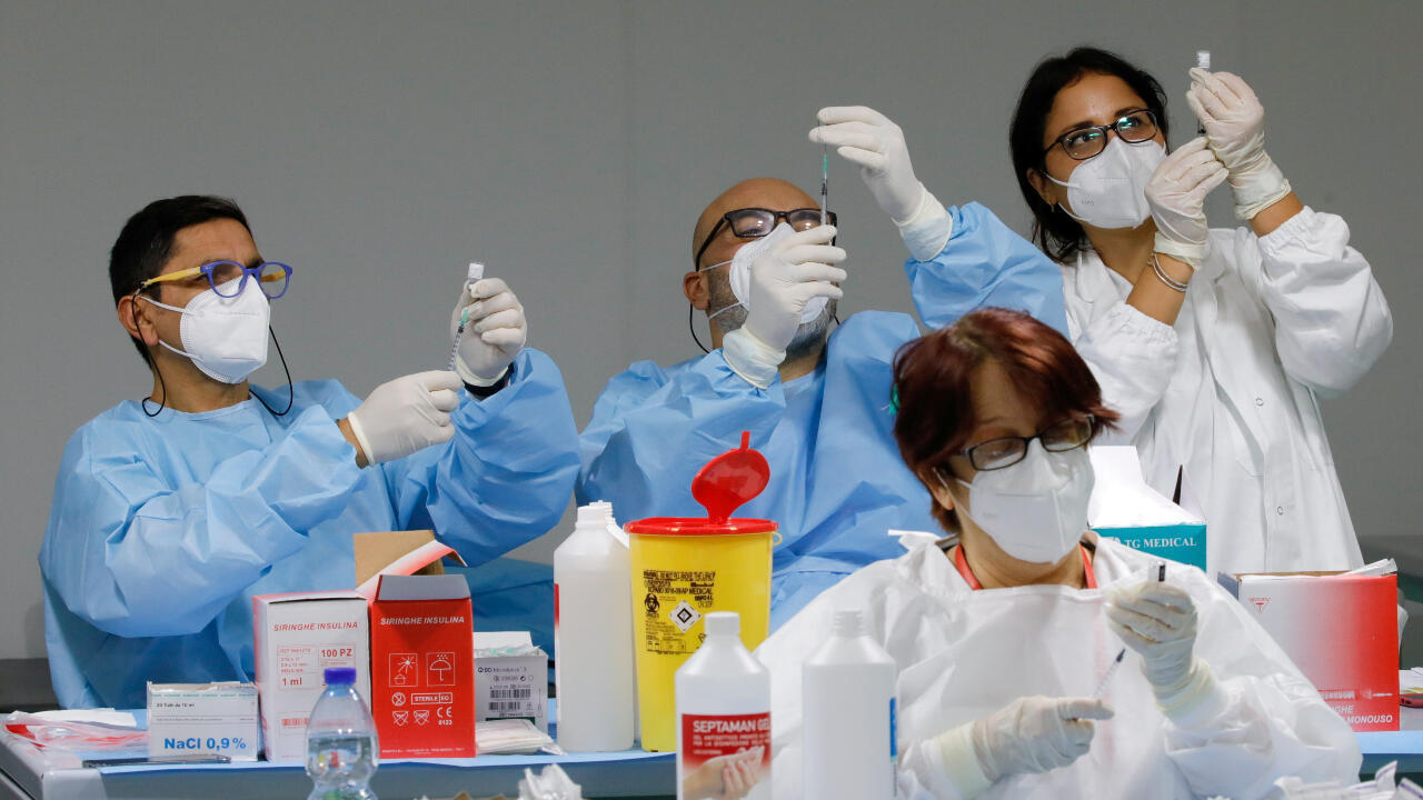 Healthcare workers prepare doses of the Pfizer-BioNTech COVID-19 vaccine at a coronavirus disease (COVID-19) vaccination center in Naples, Italy, on January 8, 2021.