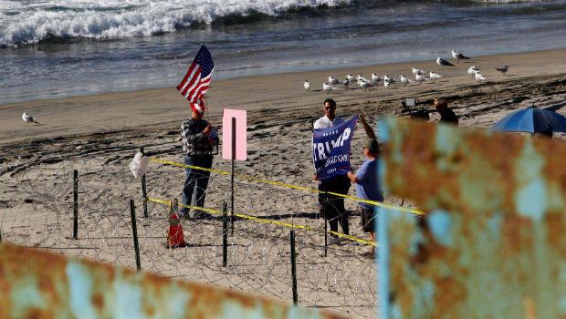 Simpatizantes del presidente de Estados Unidos, Donald Trump, desplegaron una pancarta en San Diego, EE. UU., Y detrás de la barrera fronteriza entre México y Estados Unidos, el 14 de noviembre de 2018.