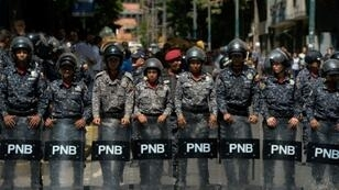 Venezuelan police stand guard near a hospital during a protest against the government of President Nicolas Maduro