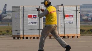A worker walks past a shipment from China of Sinopharm Covid-19 coronavirus vaccine at Phnom Penh International Airport on February 7