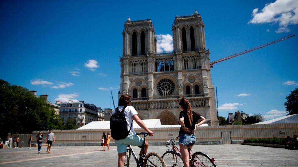 Unos paseantes se detienen en la explanada de Notre Dame en París, Francia, que reabrió por primera vez en más de un año este domingo 31 de mayo de 2020.
