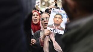متظاهرة جزائرية ترفع صورة الناشط كريم طابو مطالبة بالافراج عنه في 24 كانون الثاني/يناير 2020