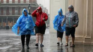 Des touristes sous les pluies diluviennes causées par le passage de Barry, dans le quartier français de la Nouvelle-Orléans, en Louisiane, le 13 juillet 2019.
